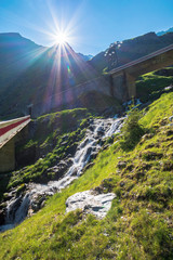cascades of balea stream in fagaras mountains. road bridge above the grassy meadows. rocky formations in sunlight. beautiful summer scenery © Pellinni