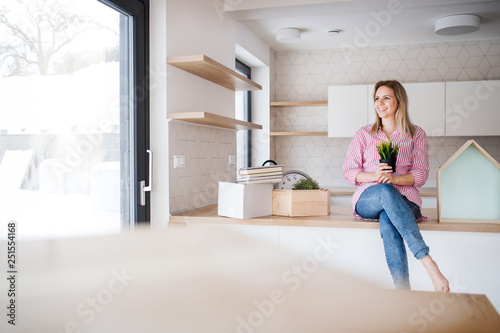 A young woman moving in new home, sitting on a counter in the kitchen. - 251554168