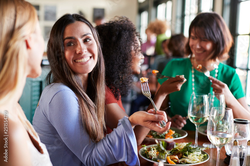 Leinwandbild Motiv Group Of Female Friends Enjoying Meal In Restaurant Together
