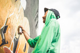 Graffiti artist painting with color spray on the wall - Focus on his hand