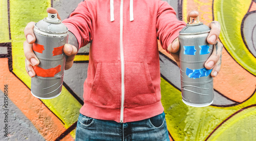 Graffiti artist painting with color spray on the wall - Focus on hands bottles