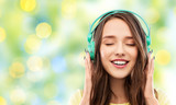 music, technology and people concept - happy young woman or teenage girl with headphones over summer green lights background