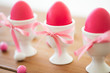 easter, food and holidays concept - pink colored eggs in ceramic cup holders with ribbon and candy drops on wooden table