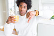 African American man holding and drinking glass of orange juice with angry face, negative sign showing dislike with thumbs down, rejection concept
