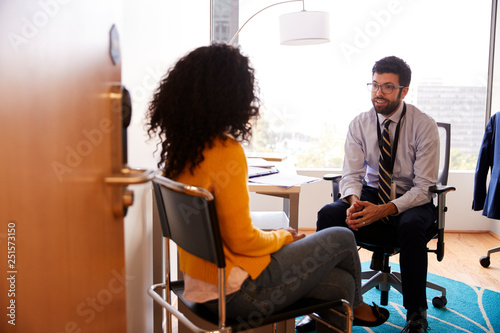 Woman Having Consultation With Male Doctor Viewed Through Door Of Hospital Office