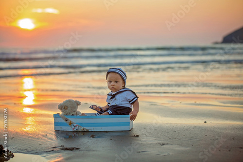 Leinwanddruck Bild Sailor baby boy, cute child, playing on the beach with wooden boat, fishes and fishing rod on sunset
