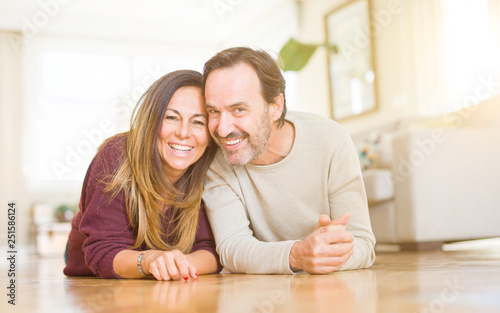 Leinwanddruck Bild Beautiful romantic couple sitting together on the floor at home
