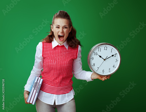 angry student woman with textbooks showing white round clock