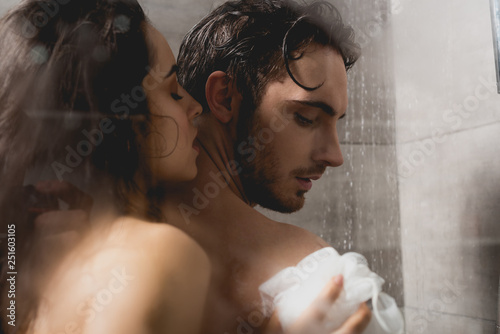 Leinwandbild Motiv handsome man and attractive woman hugging and taking shower with loofah