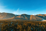 Bright panorama of mountain ranges with snow on the tops against the blue sky in winter. High mountains in the sun. Green hills and dense forests. Pine forests. Relax. Drone