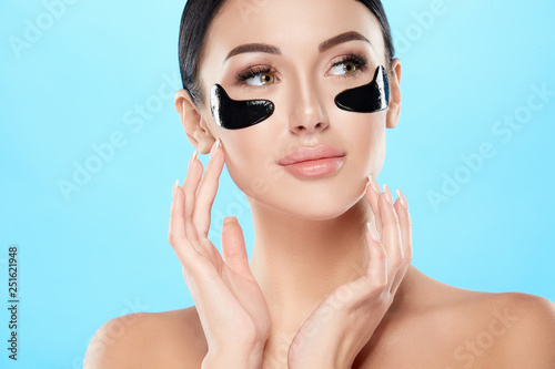 Pretty girl with nude make up and naked shoulders at studio background,black eye patches on face, skin treatment, SPA concept.