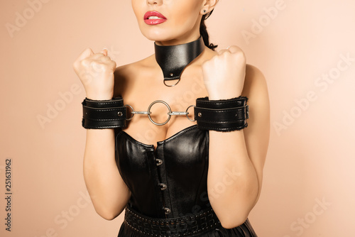 Leinwandbild Motiv Submissive girl in leather black corset, handcuffs and collar waiting for punishment