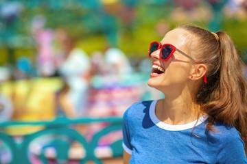 smiling traveller woman in amusement park having fun time