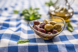 Green and red olives in bowl with olive oil and carafe in the background
