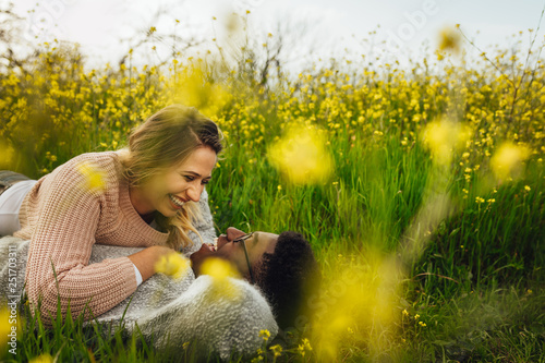 Leinwanddruck Bild Smiling couple lying on meadow outdoors