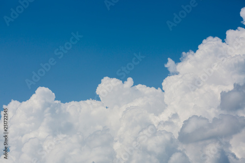 fluffy white cloud above clear blue sky background - 251722545