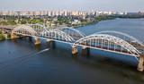 Aerial top view of automobile and railroad Darnitsky bridge across Dnieper river from above, Kiev (Kyiv) city skyline, Ukraine