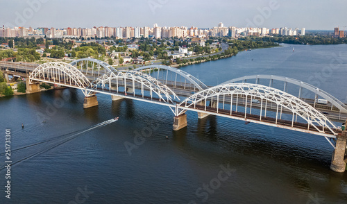 Aerial top view of automobile and railroad Darnitsky bridge across Dnieper river from above, Kiev (Kyiv) city skyline, Ukraine - 251731301