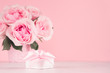 Wedding decor and gift for home in romantic style -pastel pink roses in basket and gift box with silk ribbon on white wood table, copy space.