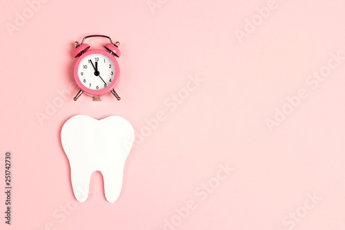 White tooth with alarm clock on pink background. Time to dental health. Dentist day concept. - 251742730