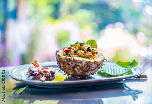 Fried rice with seafood served in a pineapple with colorful background. © somchairakin