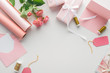 Leinwanddruck Bild - top view of pink roses, rolls of paper, wrapped gifts, envelope and greeting card on grey background
