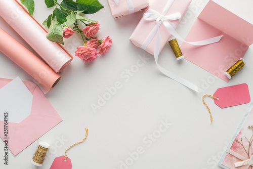 Leinwanddruck Bild top view of pink roses, rolls of paper, wrapped gifts, envelope and greeting card on grey background