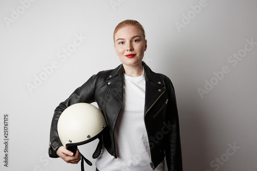 Handsome woman wearing black leather jacket and holding moto helmet smiling on white background. Fashion, glamour and moto wear concept