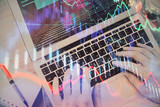 Hands typing on laptop. Business and Financial concept. Double exposure of stock market charts. - 251818556