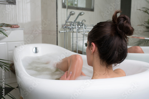 Young woman relaxing in foam bath, brunette enjoying the aromatherapy. Beauty skin care treatment - 251818930