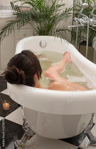 Young woman relaxing in foam bath, brunette enjoying the aromatherapy. Beauty skin care treatment - 251821187