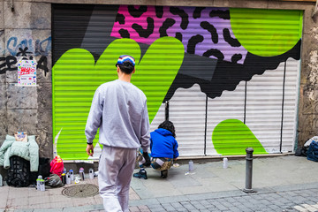 A couple practising street art at Malasaña, Madrid, Spain