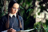 Brunette girl with braids in glasses wearing uniform listening music and reading something at the notebook while standing near the window