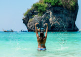 Young woman splashing water to the air on a Crystal clear water with beautiful sunny day and blue sky.