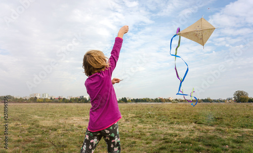 Happy little girl with a kite © pikselstock
