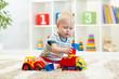Leinwandbild Motiv Nursery baby plays block and car toys sitting on carpet indoors