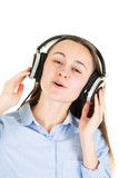 Beautiful young woman in headphones listening to music and singing on white background