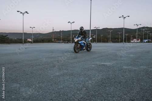 A guy on a motorcycle is going at a speed on the road. Helmet, road, motorcycle, sunset, romance, spring.