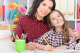 Mother and daughter drawing together  in room