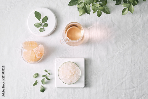 Aromatherapy. Small glass bottles with cosmetic oils. Bath salt. Fresh leaf. Objects for spa procedures on white background oil, leaf. © makistock