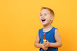 Leinwanddruck Bild - Kid boy 3-4 years old in blue shirt brush his teeth with toothbrush isolated on bright yellow orange wall background, children studio portrait. People, childhood lifestyle concept. Mock up copy space.