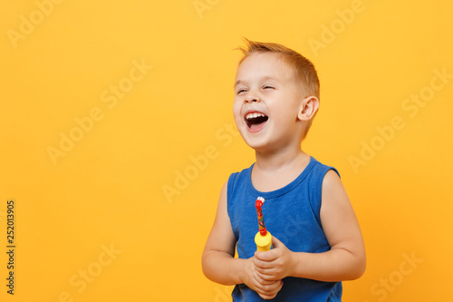 Leinwanddruck Bild Kid boy 3-4 years old in blue shirt brush his teeth with toothbrush isolated on bright yellow orange wall background, children studio portrait. People, childhood lifestyle concept. Mock up copy space.