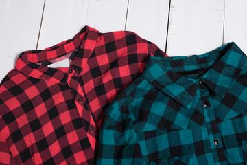 Fashion clothes. Collars of a red and green checkered shirt on white wooden floor planks