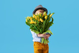 Fototapeta Tulipany - Cute smiling child holding a beautiful bouquet of yellow tulips in front of his face isolated on blue. Little toddler boy gives a bouquet to mom © shcherban