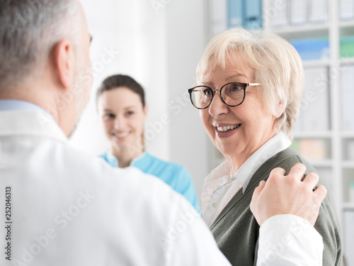 Leinwanddruck Bild Smiling senior lady meeting a doctor at the clinic