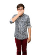 Teenager man with flower shirt and glasses covering mouth with hands for saying something inappropriate over isolated white background