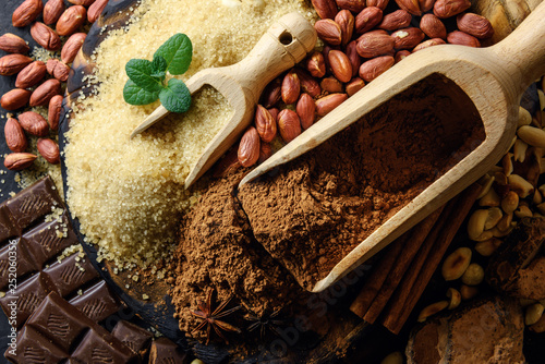 Leinwanddruck Bild Cocoa powder, chocolate, nuts and spices on a wooden table. Food photography