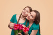 Mother and daughter with flowers posing for camera