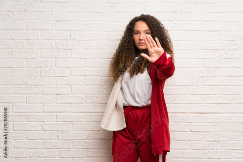 Teenager sport girl with curly hair making stop gesture denying a situation that thinks wrong