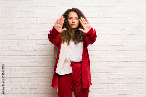 Teenager sport girl with curly hair making stop gesture and disappointed